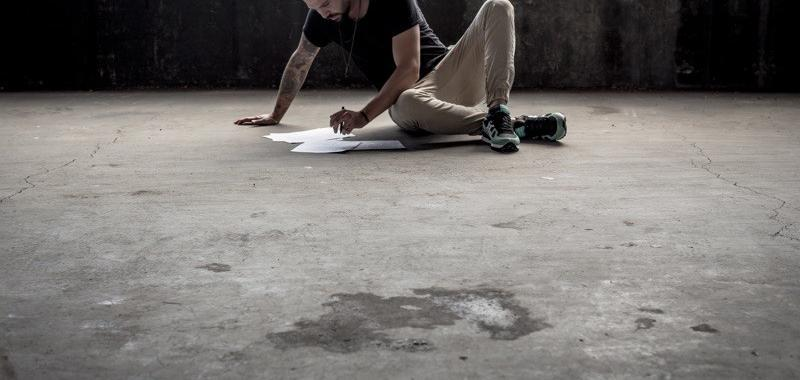 Man sat on ground writing at an agle